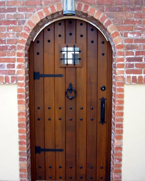 Wooden Entry Door with Wrought Iron Clavos, Pull Handles, Door Grille, and Strap Hinges.