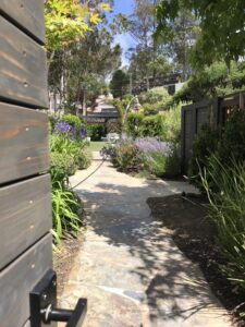 modern nero gate latch on privacy gate leading to stunning yard filled with flowers and a winding path