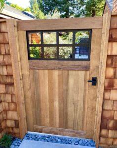 Custom wood gate with wood gate stops. Modern Nero gate latch on cedar gate with metal window frame.